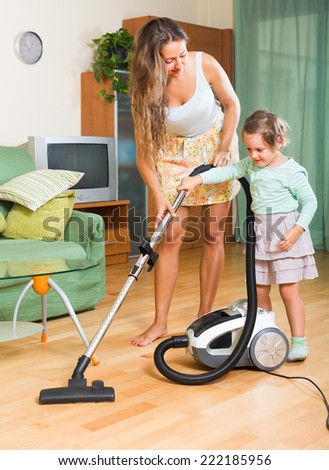 Happy mother and young daughter are doing house cleaning