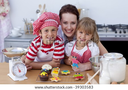 Happy mother baking with children in the kitchen - stock photo