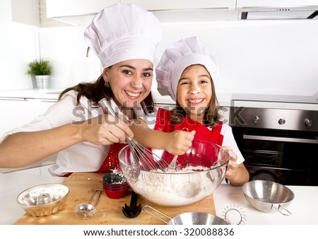 happy mother baking with little daughter in apron and cook hat working with flour , bowl and spoon preparing dough teaching the kid baking and having fun together - stock photo