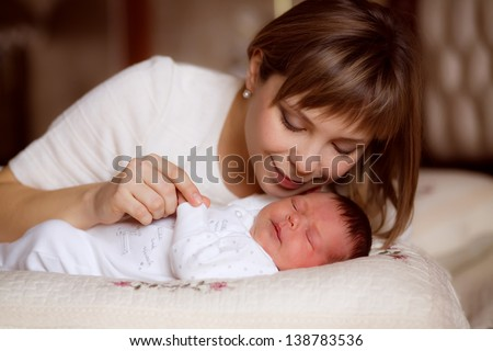 happy mother breast feeding her baby infant - stock photo