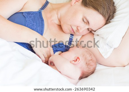 Happy mother breast feeding her baby infant. Sleeping together - stock photo