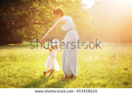 Happy mother dancing with her daughter - stock photo