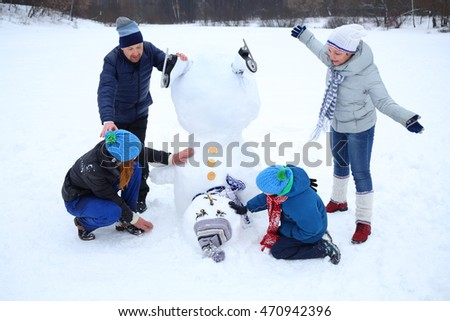 Happy mother, daughter, father and son play with snowman at winter day