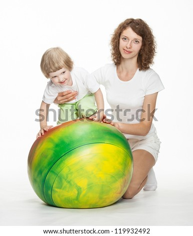 Happy mother doing sport exercises with little daughter; white background