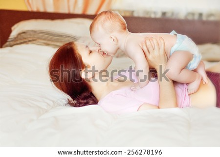 Happy mother embrace baby boy, focus on mother. Instagram filter. - stock photo