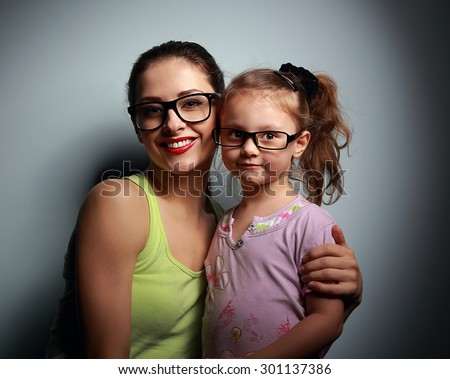 Happy mother embracing cute girl in fashion black glasses and looking with love on dark background - stock photo