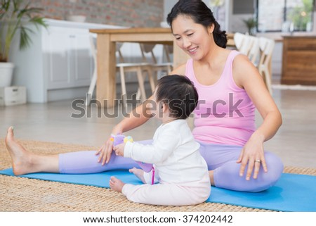 Happy mother exercising on mat while looking at baby daughter at home - stock photo