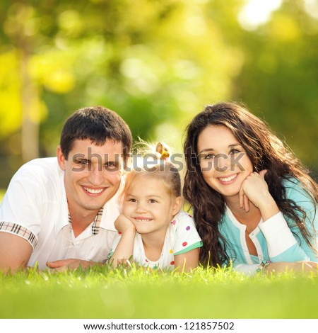 Happy mother, father and daughter in the park. Beauty nature scene with family outdoor lifestyle. Happy family resting together on the grass, having fun outdoor. Happiness and harmony in family life.