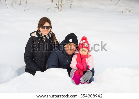 Happy mother,father and daughter posing in snow