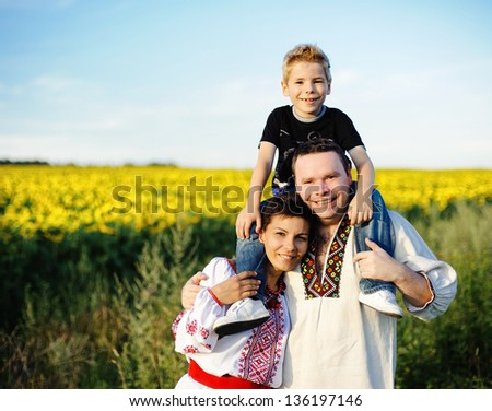 Happy mother, father and son on the field with sunflowers