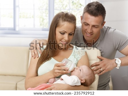 Happy mother feeding and caressing newborn baby, father hugging them. - stock photo