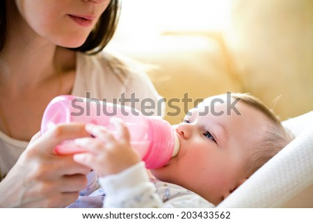 happy mother feeds the baby bottle - stock photo