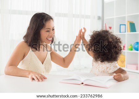 Happy mother giving high five to her little daughter - stock photo