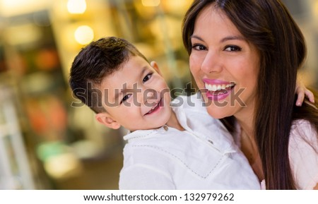 Happy mother having fun with her son at the mall - stock photo