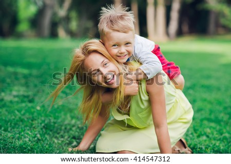 Happy mother having fun with her son on grass. A young mother piggybacking her son in the park