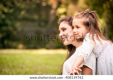 Happy mother having great time together with her daughter in nature - stock photo