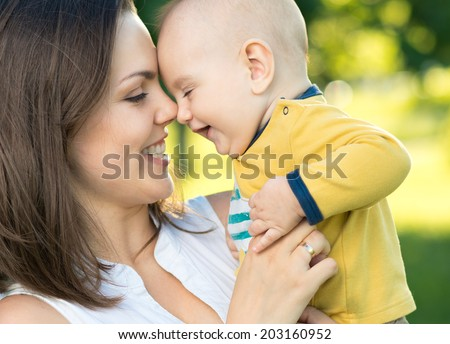 Happy mother holding a young son in the park - stock photo