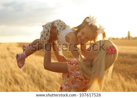 happy mother holding baby smiling on a wheat field in sunlight - stock photo