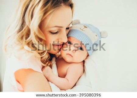 happy mother holding her baby. little boy in hat.