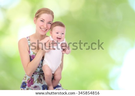 happy mother holding her baby. On an abstract green background - stock photo