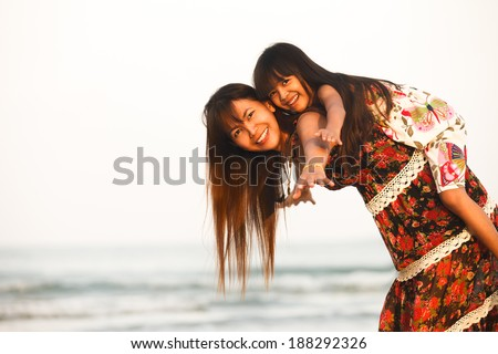 Happy mother holding her daughter on the beach - stock photo
