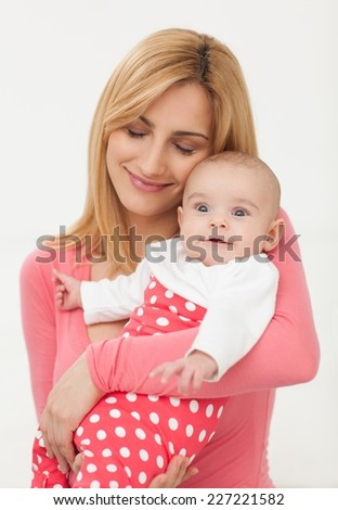 Happy mother holding her 3 months old daughter. - stock photo
