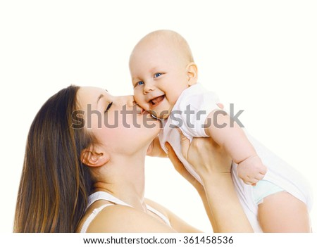 Happy mother holding on hands and kissing her cute baby over white background