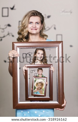 Happy mother holding portrait with her family each is located inside their own frame - stock photo