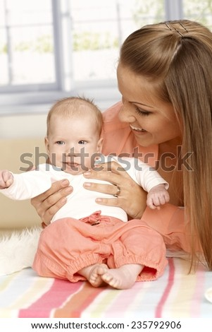 Happy mother holding tiny newborn baby, looking at her. - stock photo
