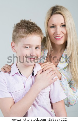 Happy mother hugging smiling son in pink shirt with disheveled hair in the studio - stock photo