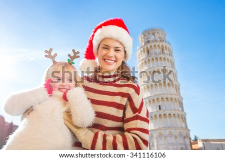 Happy mother in Christmas hat and cosy sweater and daughter wearing funny reindeer antlers standing in front of Leaning Tour of Pisa, Italy. They spending exciting Christmas time traveling. - stock photo