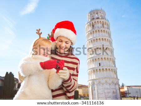 Happy mother in Christmas hat and daughter wearing funny reindeer antlers checking photos on camera in front of Leaning Tour of Pisa, Italy. They spending exciting Christmas time traveling. - stock photo