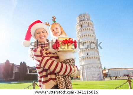 Happy mother in Christmas hat and daughter wearing funny reindeer antlers holding gift box in front of Leaning Tour of Pisa, Italy. They spending exciting Christmas time traveling. - stock photo