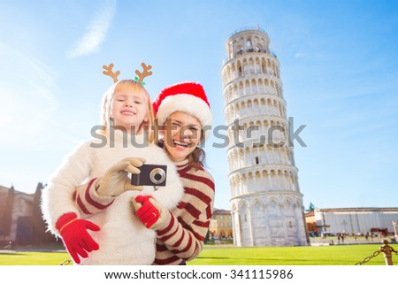 Happy mother in Christmas hat and daughter wearing funny reindeer antlers taking photos in front of Leaning Tour of Pisa, Italy. They spending exciting Christmas time traveling. - stock photo