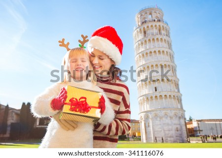 Happy mother in Christmas hat hugging daughter wearing funny reindeer antlers and holding gift box in front of Leaning Tour of Pisa, Italy. They spending exciting Christmas time traveling. - stock photo