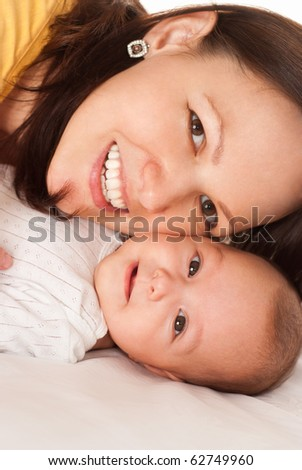 happy mother in yellow holding  newborn