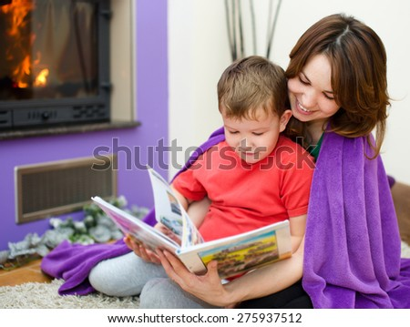 Happy mother is reading book with her son