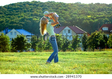 Happy mother keeps small girl on hand - stock photo