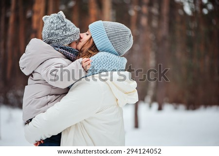 happy mother kissing baby girl on the walk in winter snowy forest  - stock photo