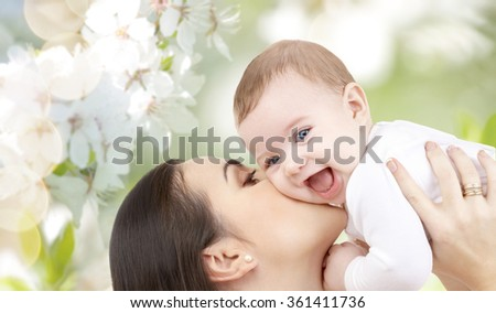 happy mother kissing her baby over cherry blossom
