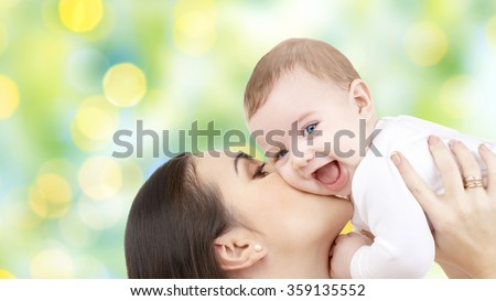 happy mother kissing her baby over green lights - stock photo