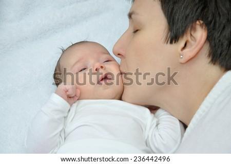 Happy mother kissing her lovely newborn baby girl - stock photo