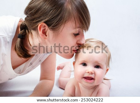 Happy mother kissing smiling child baby - stock photo