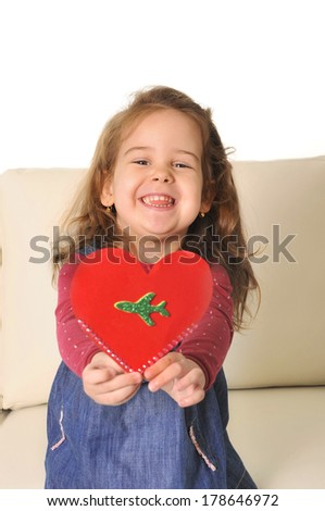 Happy Mother kissing sweet  little daughter and reading fairy tales book on couch together - stock photo