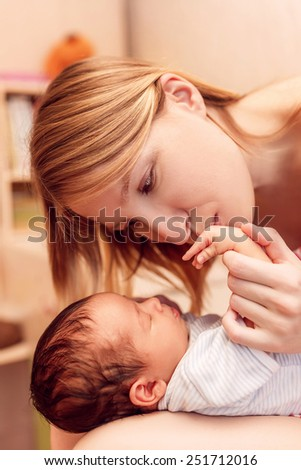 Happy mother kissing the hand of a newborn, closeup - stock photo