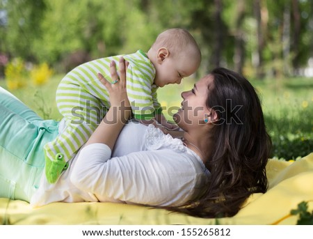 Happy mother lay with newborn baby on grass in park  - stock photo