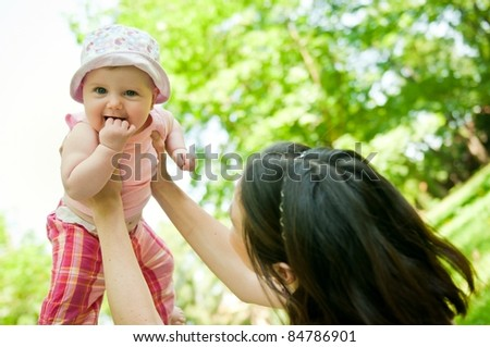 Happy mother lifting her beautiful child outside in park - stock photo