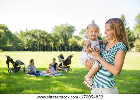 Happy mother looking at cute daughter with friends and children in background at park - stock photo