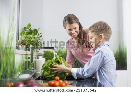 Happy mother looking at son washing vegetables in kitchen - stock photo