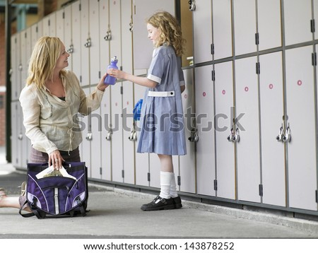 Happy mother packing daughter's school bag near school lockers - stock photo